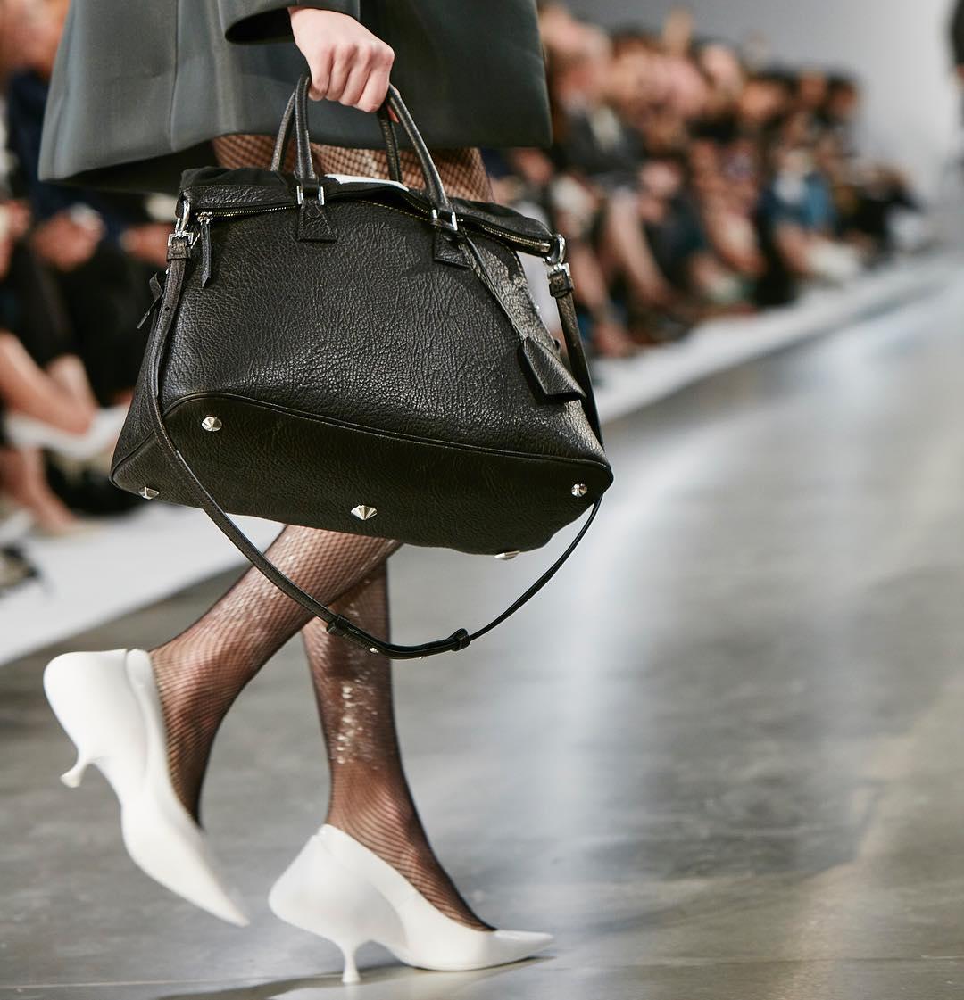 メゾンマルジェラのバッグを持って歩く女性